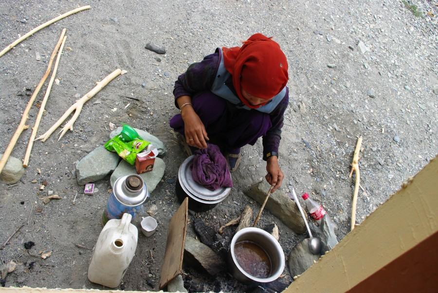 Женщина готовит чай в деревне, Гималаи, Индия