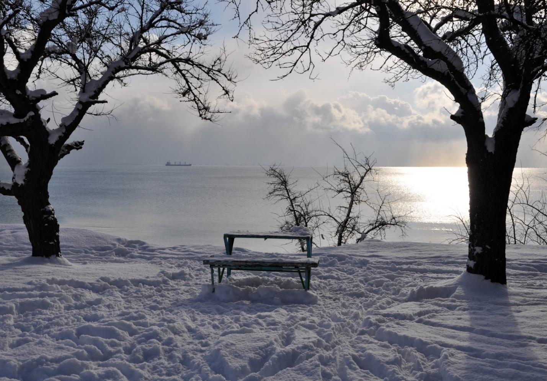 Лавочка в снежном парке и зимнее Черное море. Керчь, Крым