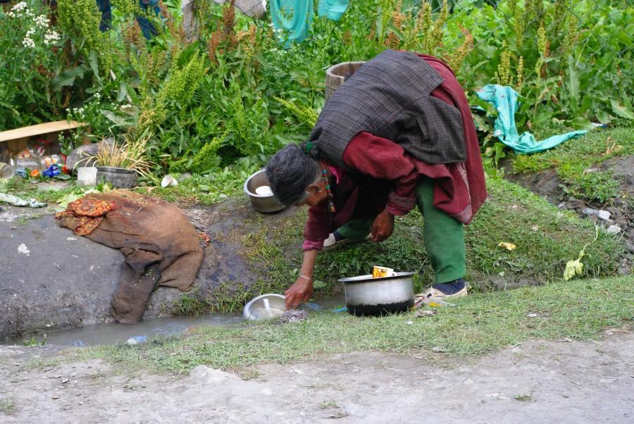 Женщина моет посуду в ручье, Гималаи, Индия