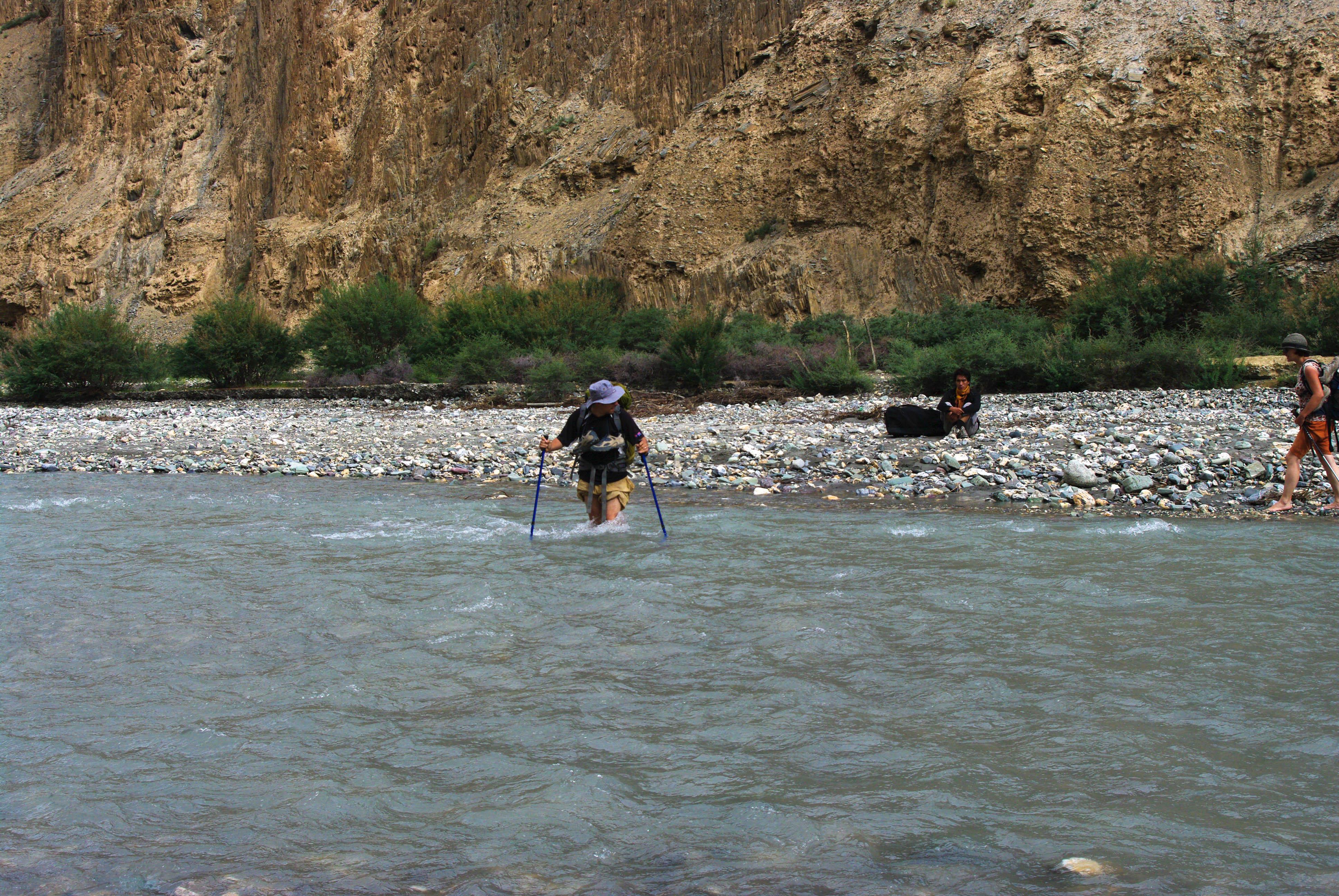 Туристы в брод через реку в Гималаях