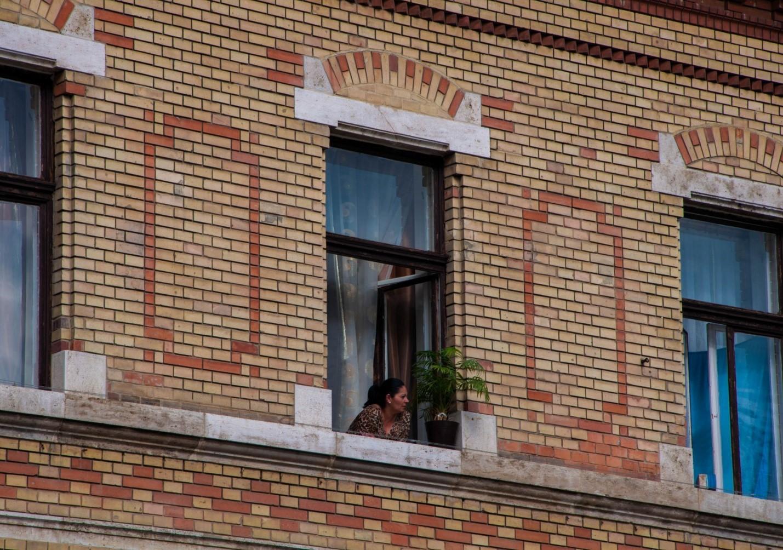 Женщина выглядывает из окна в Будапеште