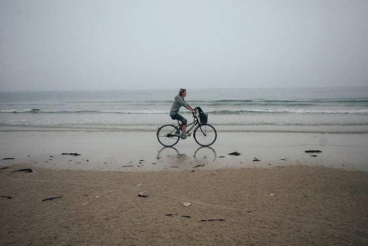 Девушка на велосипеде по пляжу