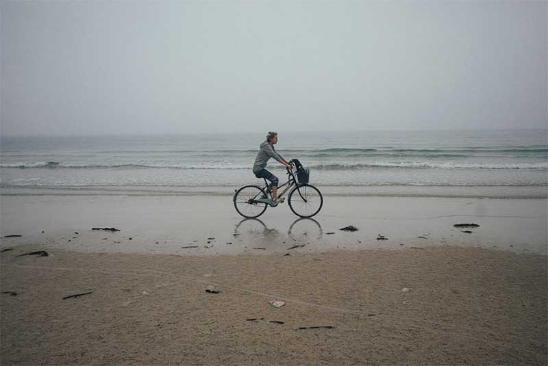Девушка на велосипеде по берегу моря, океана